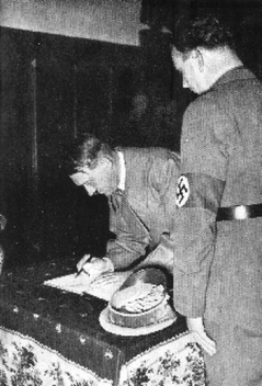 Hitler signs the Eger city book,  inside the Rathaus