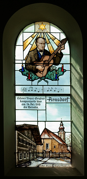 Light filters through the stained glass window depicting Franz Xaver Gruber and the Arnsdorf schoolhouse.