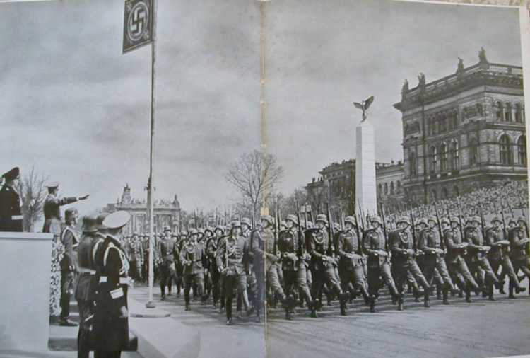 Hitler saluting passing soldiers.